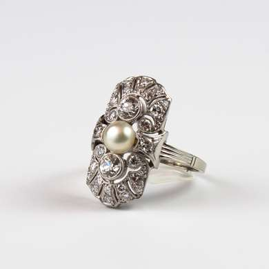 Art Deco Platinum Ring set with a pearl button and two diamonds at the center.