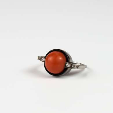 Art Deco platinum ring set with a cabochon coral surrounded by black enamel and 4 small old cut diamonds.