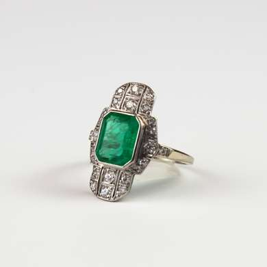 Art Deco platinum ring set with a central emerald surrounded by old size diamonds.