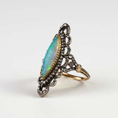 Marquise gold ring set with an opal in an entourage of chips diamonds.