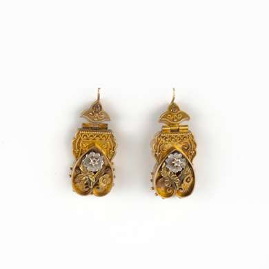 Pair of earrings in gold representing inverted hearts decorated with a filigree work and flowers in three shades of gold set with small diamonds.