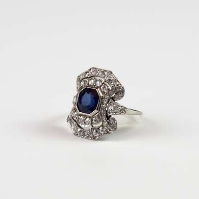 Platinum ring set with a sapphire highlighted by 6 small calibrated sapphires, framed by old size brilliant.