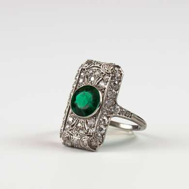 Rectangular ring in beading white gold openwork set with old size diamonds surrounding an emerald in the center.