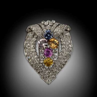 Shieldlike brooch platinium set with brilliants and multi colored sapphires in the centre