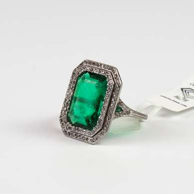 White gold ring set with an emerald surrounded by old size diamonds.