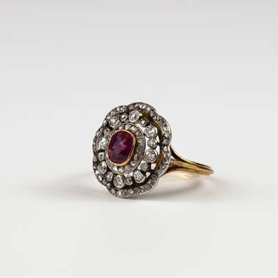 Yellow gold ring set with a ruby oval surrounded by a row of 16 old cut diamonds and two rows of small roses.